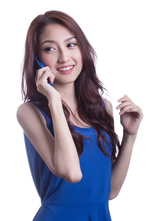 Young Woman smiling and texting on her mobile phone, isolated over white background. photo