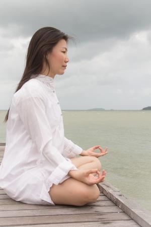 dhyana: Meditazione di giovani donne in abito bianco su un ponte sul mare. Archivio Fotografico