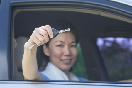 Happy smiling woman with car key. Driving. photo