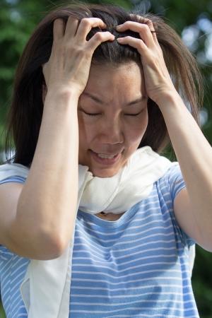 Asiatische Frauen haben eine starke Kopfschmerzen. Standard-Bild - 21499790