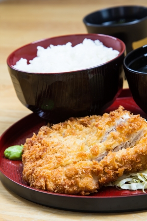 Fried breaded pork served with steamed rice and soup. photo