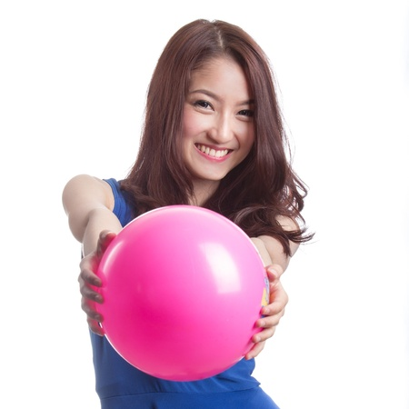 attractive asian woman playing with ball on white background
