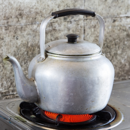 Aluminum tea kettle is on the stove.