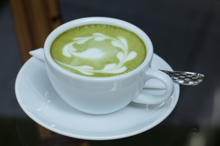 Green tea beverage in a white cup.