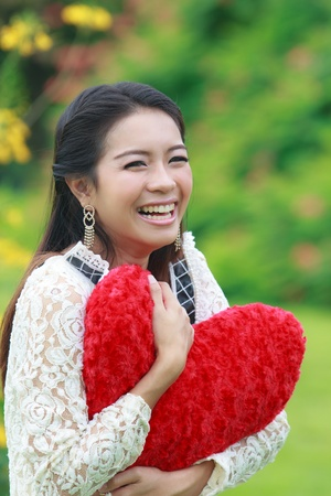 Cute young Asian woman holding a red heart-shaped pillow.