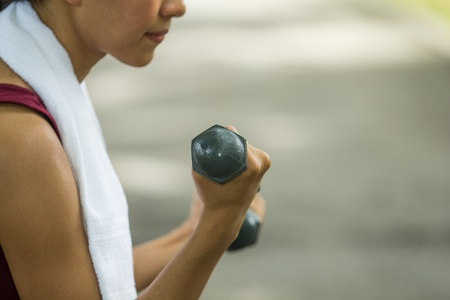 woman lifting weights: Beautiful woman holding weights in her hands