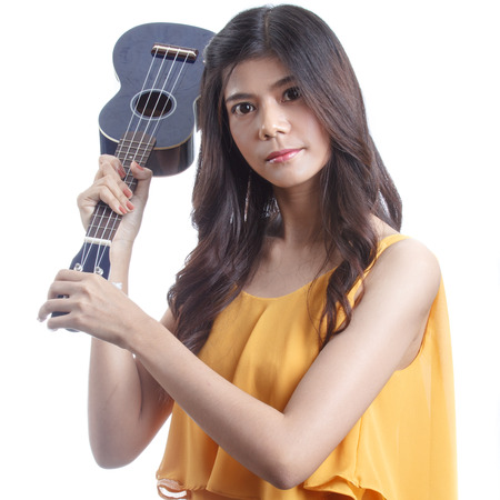 Asian woman holding angry ukulele in hand. photo