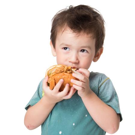 Handsome boy eating a big burger.