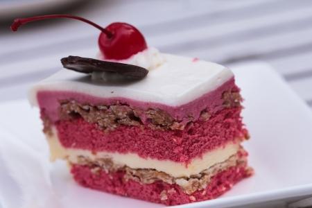 to cake layer: Torta di fragole strato topping con la ciliegia Archivio Fotografico