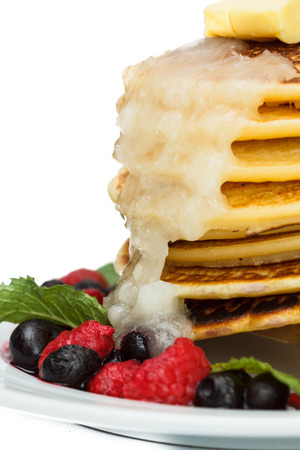 Pancakes with berries on a white plate. photo
