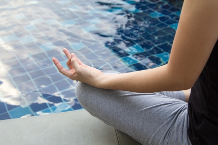 Young woman sitting poolside relaxation and meditation.