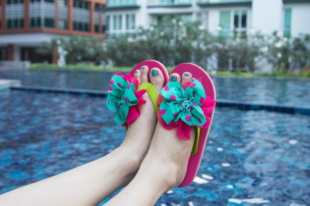 painted toes: Pair of sandals sitting on the edge of a pool.