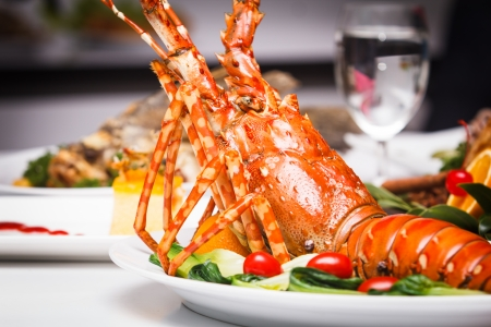 lobsters: a luxury dish of lobster roasted and decorated with many items of vegetable Stock Photo