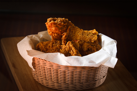 Fried Chicken in a basket on a wooden floor. photo