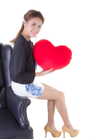 Asian woman holding a red heart-shaped pillow. photo