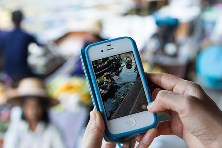 RATCHABURI, THAILAND - MARCH 7, 2014 : Close up shot of Woman's hand holding the phone and taking a photo of people selling goods on the wooden boats at  ancient Damnoen Saduak floating market by the camera app on an Apple iPhone 4s.