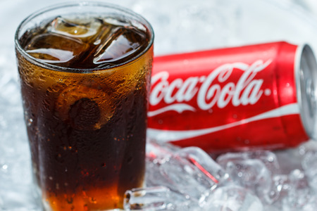 BANGKOK, THAILAND - MARCH 21, 2014 : Can of Coca-Cola lying on ice. Coca-Cola is the one of the worlds favourite soft drinks.