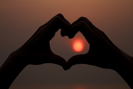 Woman lifts hands up to sky in the heart shape around the sun photo