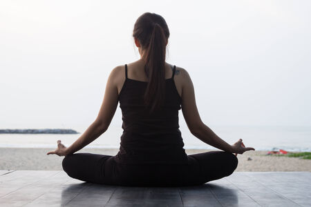 portrait back view of Asian woman practicing yoga at peace sea in morning photo