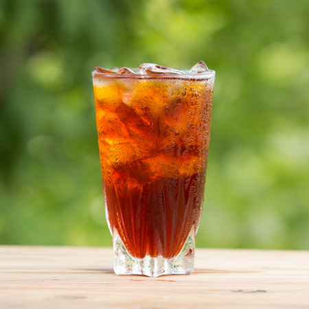 Glass of ice tea on a wooden table photo