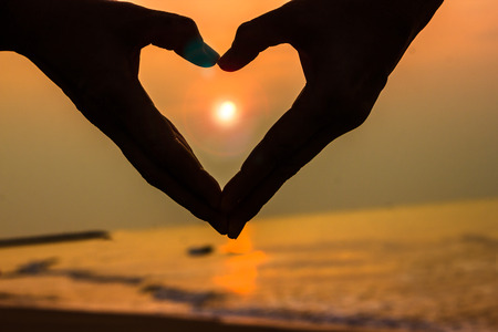 Woman lifts hands up to sky in the heart shape around the sun, sea background photo