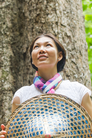 Vietnamese woman holding hat looking at something in the forest photo