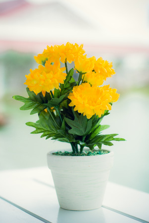 whote: yellow Artificial Flowers on whote wooden table