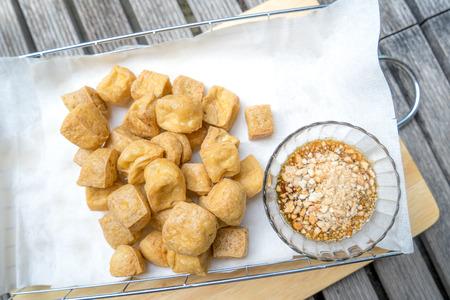 Gebratener Tofu mit würziger Erdnusssoße auf Schneidebrett Standard-Bild - 34243915