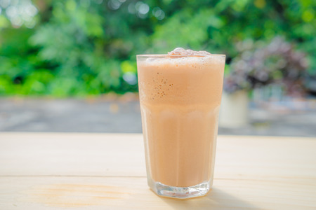 Milch Tee-Smoothie auf Holztisch im Garten Standard-Bild - 34275506