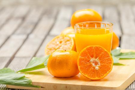 Orangensaft und Orangen auf dem Schneidebrett Standard-Bild - 34275530