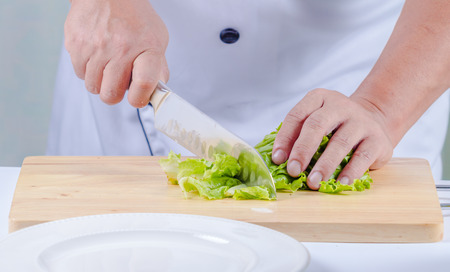 cutting bord: chef cutting lettuce on cutting bord for vegetable salad