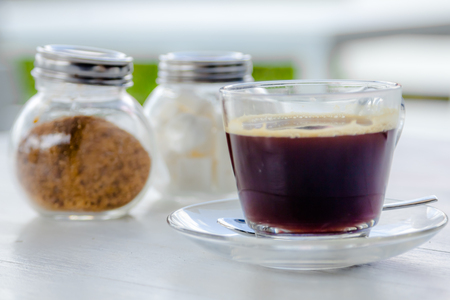 suger: black coffee with cube sugar and red suger on table