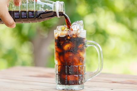 Auslaufender schwarzer Kaffee in ein Glas auf Holztisch Standard-Bild - 35519264