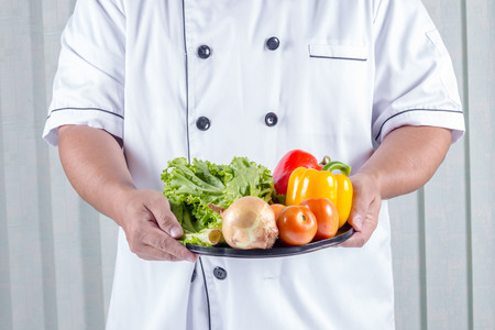 bell peper: chef holding Many types of vegetables on a plate