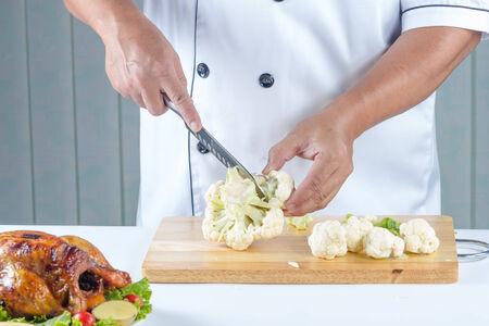 cutting bord: chef cutting vegetable name cauliflower on cutting bord Stock Photo