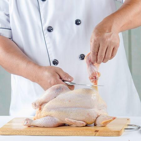 cutting bord: chef cutting raw chicken on cutting bord