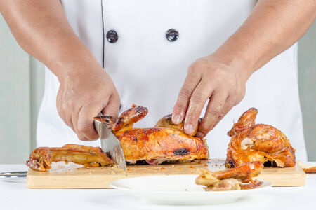 cutting bord: chef cutting roast chicken on cutting bord Stock Photo