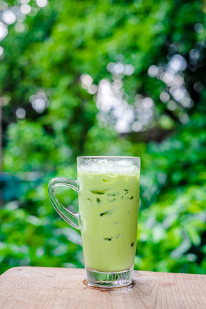 quencher: green tea with glass on nature background Stock Photo
