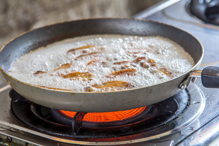 stainless steel range: old frying pan with boiling oil on the stove.