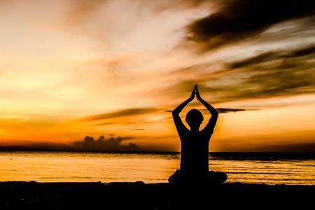yoga beach: women playing yoga at beachside on sunset Stock Photo