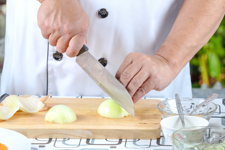 concoct: Chef sliced onions on a wooden cutting board. Stock Photo