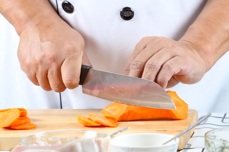 concoct: Chef sliced carrot on a wooden cutting board.