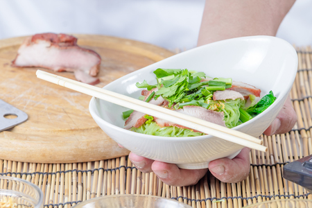 hand holding noodle in dish photo