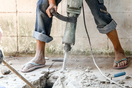 pneumatic: Builder worker with pneumatic hammer drill equipment at construction site
