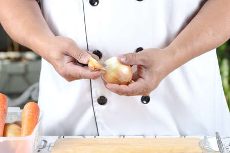 concoct: Chef peeling onions on a wooden cutting board.