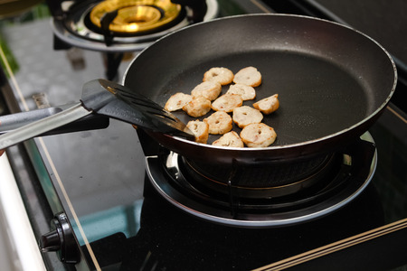 fry pork in on  frying pan stove photo