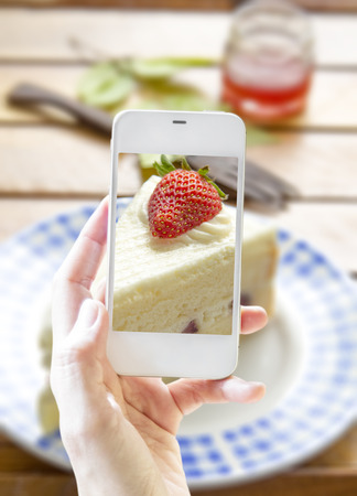 str: Hands taking photo of str awberry cheese cake on wooden