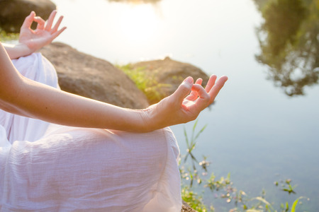 woman meditating in a yoga on natrue Stock Photo