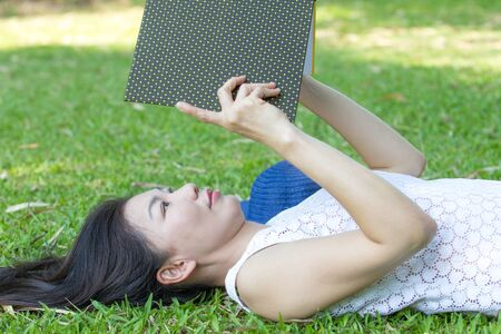 Woman reading a book on lawn photo
