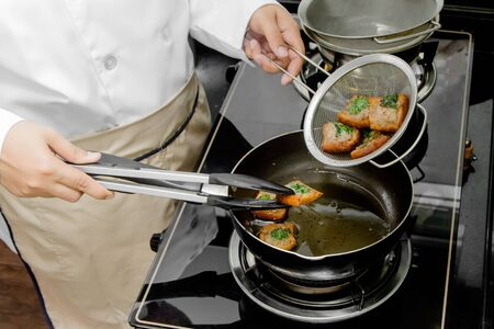 raw food: chef frying bread with raw minced pork spread in kitchen Stock Photo